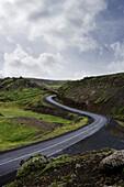 Landstraße durch Hügellandschaft, Island
