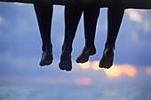 Paar sitzt auf der Kante eines Holzstegs und betrachtet den Sonnenuntergang, Entspannung, Romantik