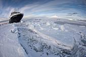 Marina Svetaeva,  Ice_strengthened Russian cruise ship ( Aurora Expeditions) in McMurdo Sound sea ice _ volcano Mt Erebus behind_ volcano Mt Erebus behind
