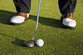 GOLF Adult middle aged male practice putting on green at public course in Deerfield,  Illinois,  address ball with putter