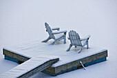 Snow covered adirondack chairs
