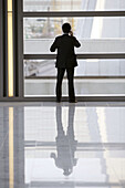 Silhouette of a Chinese man having a telephone conversation while standing in the lobby of an office building,  Hong Kong,  China,  Southeast Asia