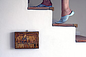 Female feet of a woman wearing traditional maroccan Babush and climbing up the stairs with a picture of a bible scene hanging on the white washed wall of an old landhouse villa,  Gabiano,  Piemont,  Italy,  Europe
