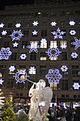 One of the famous Christmas angels of the Rockefeller Center made of wire with trumpet with Saks Fifth Avenue department store in the background which has been decorated with snow flakes designed by Svarovski, Manhattan,  New York City,  North America