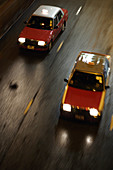 Two red blurred taxis behind each other moving in high speed on the street  in Wanchai (Wan Chai),  Hong Kong,  China,  Southeast Asia