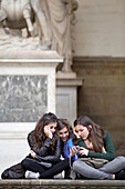 Three young girls sitting together at the Loggia dei Lanzi and looking at images of their digital camera,  Florence (Firence),  Tuscany,  Italy,  Southern Europe
