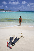 Woman standing on the beach with snorkel gear in foreground  Mopion,  St Vincent and the Grenadines  Model released