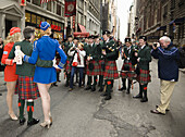 Members of St Columbas Pipe band,  involved in Tartan day Parade,  New York,  Usa with the leader being photograghed with two female models