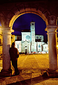 Man leant against a column looking at the Main Square and the cathedral  Night view  Sigüenza  Guadalajara province  Castile La Mancha  Spain