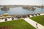 Tourists visiting Saluting Battery,  overlooking Grand Harbour,  from Upper Barracca Gardens,  Valletta,  Malta