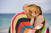 Adult, Adults, beach, beaches, Blanket, Blankets, Color, Colour, complicity, Contemporary, couple, couples, Cover, Covering, Daytime, exterior, female, Hat, Hats, Headgear, Hold, Holding, human, Intimacy, kiss, kisses, kissing, Leisure, love, male, man, m