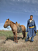 Mongolian camel herder stands beside his horse,  north central Mongolia No release available