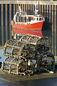Fishing boat and lobster pots sitting on the quayside Portavogie Harbour,  County Down Northern Ireland
