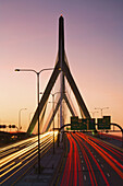 Rush hour traffic light-trails stream in and out of the city of Boston over the Leonard P Kakim Bunker Hill Bridge,  with a colorful sky in the background. Massachusetts,  USA