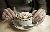 Adult, Adults, Beverage, Beverages, Cafe, Cafes, Cappuccino, Close up, Close-up, Closeup, Coffee, Coffee shop, Coffee shops, Coffeehouse, Coffeehouses, Color, Colour, Cup, Cups, detail, details, Drink, Drinks, Europe, Female, Food, hand, hands, human, ind