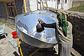 Nepalese woman cooking with a solar cooker  Annapurna Circuit,  Nepal