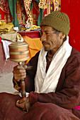 A man using a hand prayer wheel at the festival of Lama Yuru monastery Ladakh,  India