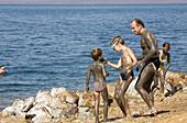 Jordan,  Dead Sea People on the beach with Dead Sea mud on their bodies