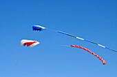 Two colorful kites flying against a clear blue sky
