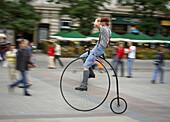 Poland,  Krakow,  Main Market Square,  man rides an old bicycle