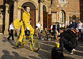 Funny street performer on bicycle at Main Market Square,  Krakow,  Poland