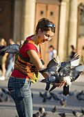 Poland,  Krakow,  Main Market Square,  pigeons and young woman having fun