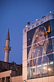 building with roof terrace, advertising and Selman Aga Camii mosque in background, Uskudar, Istanbul, Turkey