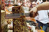 Süßigkeiten, Verkauf, mit einem großen Messer wird ein Stück von der Turmform abgeschnitten, Türkischer Honig, Halva mit Pistazien, Istanbul