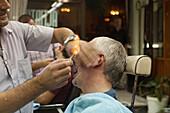 Friseur, Barbier, traditionelle Rasur eines Touristen, mit Rasiermesser, Abflammen der Ohrenhaare, Istanbul