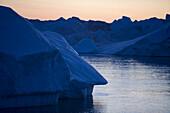 View at blue icebergs from Ilulissat Kangerlua Icefjord at dusk, Ilulissat (Jakobshavn), Disko Bay, Kitaa, Greenland