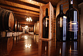 Wine cellar with wine barrels and wine bottles, Backsberg estate, Paarl, South Africa, Africa