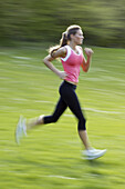 Young woman wearing a pink top, jogging through green fields, Bavaria, Germany