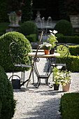 Cultivated garden with wrought iron garden furniture, rake, watering can, Munich, Bavaria, Germany