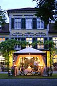 Elegant setting with wrought iron garden furniture under garden pavillon, Munich, Bavaria, Germany