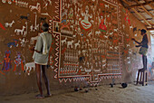 Men painting tribal art on a wall in a ceremonial hall, Bastar, Chhattisgarh, India, Asia