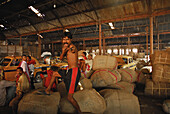 Men at a warehouse at Howrah Station in the evening, Howrah, India, Asia