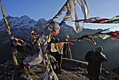 Trekkers and prayer flags at Dzongri La, Trek towards Gocha La in Kangchenjunga region, Sikkim, Himalaya, Northern India, Asia