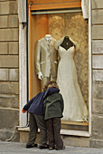 Two children embracing in front of shop window with bride's gown, Grosseto, Tuscany, Italy, Europe