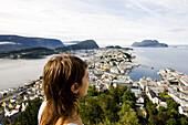 Junge Frau schaut auf die Stadt Alesund unter Wolkenhimmel, More og Romsdal, Norwegen, Skandinavien, Hafenstadt, Europa