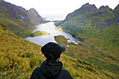 Young woman looking at lake Agvatnet surrounded by mountains, Lofoten, Norway, Scandinavia, Europe