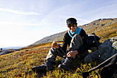 Laughing young woman sitting on the ground tying her shoes, Sjurfjellet Saltar, Norway, Scandinavia, Europe