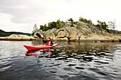 Young woman kayaking at the rocky coastline, Skaggerak, Sorland,  Norway, Scandinavia, Europe