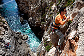A young man, a climber, a sportclimber, freeclimber, climbing on the cliffs at the bay of Zurrieq, Malta, Europe