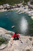 A young man climbing above the Inland Sea in the sunlight, Dwerja Bay, Gozo, Malta, Europe