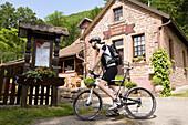 Cyclist reading menu of Restaurant au Wasigenstein, Wengelsbach, Niedersteinbach, Alsace, France