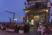Guests in a pavement cafe in the evening, Castelmola, Sicily, Italy
