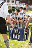 Two men wearing leather trousers carrying beer crate, May Running, Antdorf, Upper Bavaria, Germany