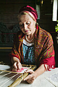 Artisan embroidering in the museum of Russian wooden architecture of Kizhi, Lake Onega, Republic of Karelia, Russia