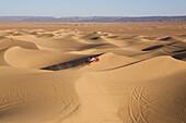 Jeep driving across the sand dunes, Dunes de Juifs, desert near Zagora, Sahara, Morocco