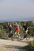 Three mountain bikers on a track at Lago Trasimeno, Umbria, Italy, Europe